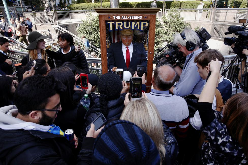 Pedestrians stop to look at and photograph a Donald Trump themed fortune telling machine. The machine became a social media hit after it popped up around the city, including in front of Trump International Hotel and Tower, the News Corp headquarters and the New York Times building. REUTERS/Lucas Jackson